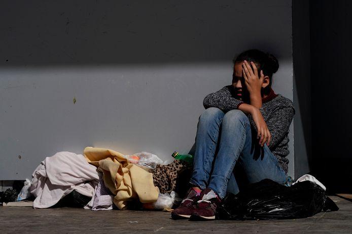 Een migrante probeert haar gezicht tegen de zon te beschermen nadat ze door Amerikaanse grenspolitie werd tegengehouden aan de grens.