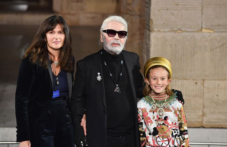 De modeontwerper met aan zijn rechterhand Virginie Viard en aan zijn linkerhand diens peetzoon Hudson Kroenig.   Beeld AFP