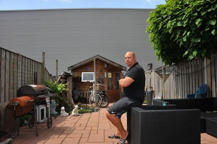 Bezwaarmaker Edwin de Visser uit de Rijksstraatweg kijkt nu al vanuit zijn achtertuin tegen de stalen wand van een bedrijfshal aan.