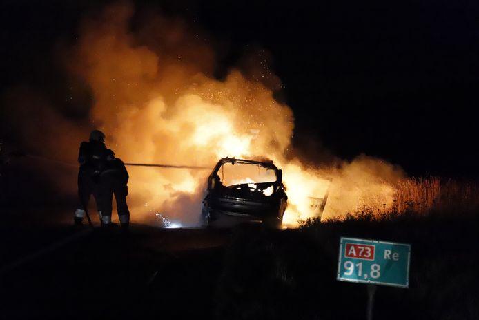 De brandweer blust de brandende auto op de snelweg A73 bij Cuijk.
