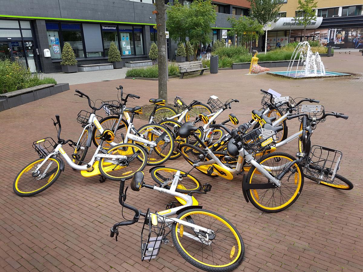 Zomaar een plein in Rotterdam: daar liggen ze dan, de deelfietsen.