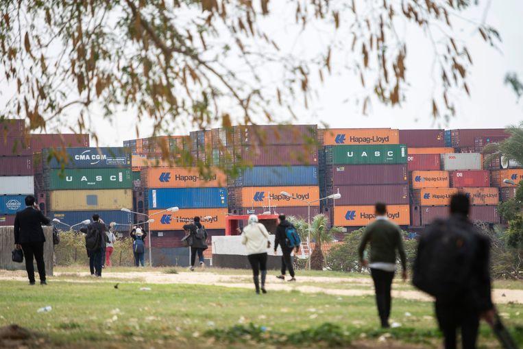 Een containerschip hervat zijn tocht door het Suezkanaal. Het schip moest dagen wachten omdat het kanaal was versperd nadat een ander containerschip, de Ever Given, was vastgelopen en de doorgang blokkeerde.  Beeld EPA
