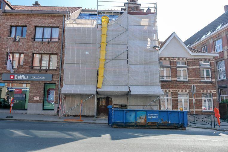 Het huis waar het gat werd gemaakt, de bank en rechts het huis van de buurman die de politie verwittigde.