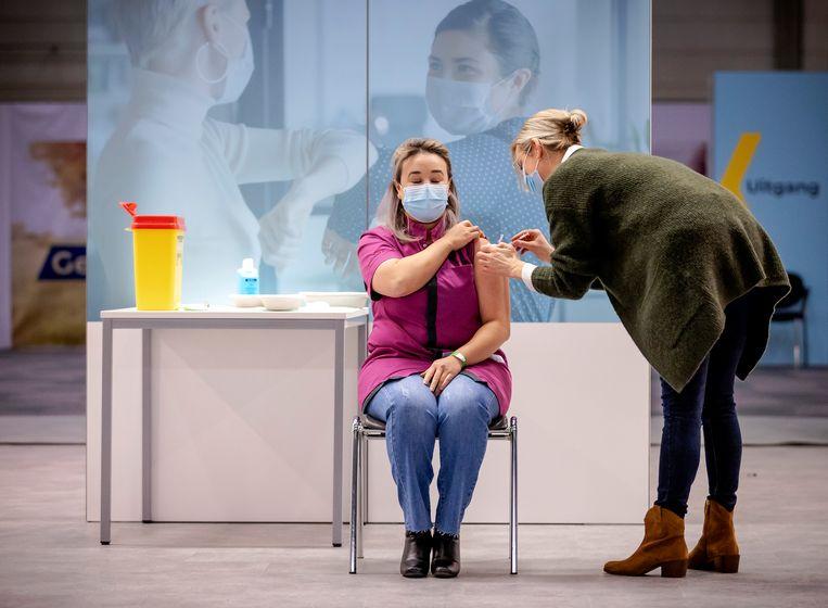 Sanna Elkadiri, medewerkster van verpleeghuis Het Wereldhuis in Veghel, krijgt het eerste vaccin.  Beeld ANP