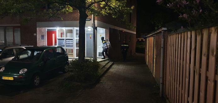 Een van de agenten loopt richting de woning waar de man zich heeft verstopt.