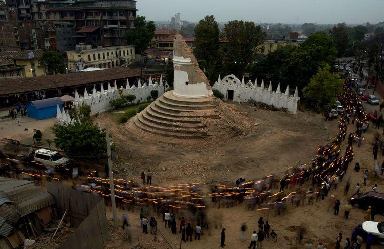 Nepalezen doen mee aan een ceremonie in Kathmandu om de slachtoffers van de aardbeving te herdenken. Beeld afp