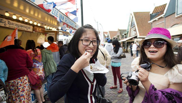 Twee Chinese vrouwen eten haring in Volendam. Beeld anp