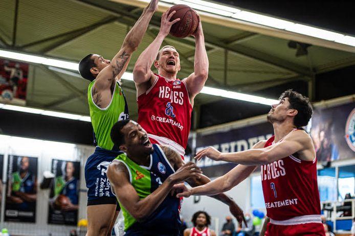 Dominic Gilbert gaat, verdedigd door Worthy de Jong van ZZ Leiden, richting de basket voor Heroes. Rechts kijkt Stefan Wessels toe.