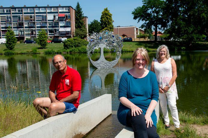 John Langen, kunstenares Iris Burghout en Alie Mulder bij het nieuwe kunstwerk in het Zuiderpark. Op de plek waar de Kayersbeek in de vijver stroomt.