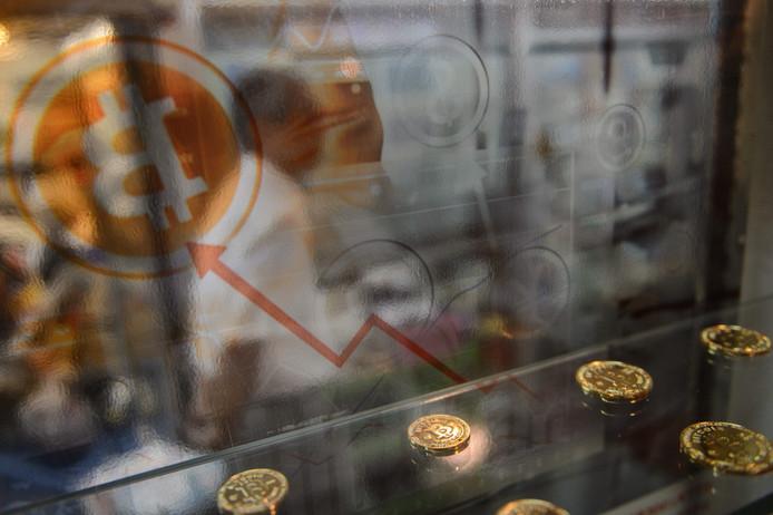Een man in Hong Kong loopt voorbij een display met bitcoins, 2016.
