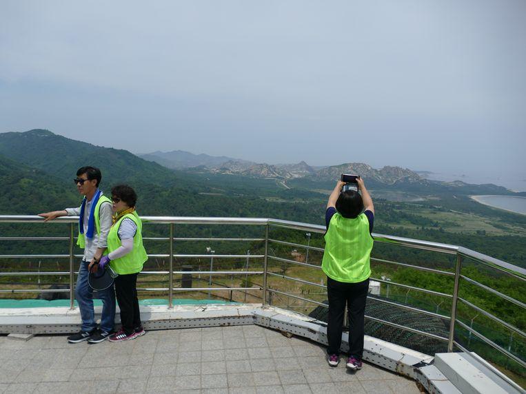 Uitzicht op de bergtoppen van Noord-Korea. 'Vorig jaar kon ik de DMZ alleen vanuit de verte zien vanaf het observatorium in Goseong. Ik ben zo blij dat ik hier nu zelf kan lopen', zegt een van de wandelaars. Beeld Jeroen Visser