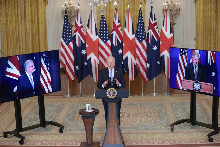 De Amerikaanse president Joe Biden tijdens zijn virtuele persconferentie met de Britse premier Boris Johnson (rechts) en de Australische eerste minister Scott Morrison (links).  Beeld EPA