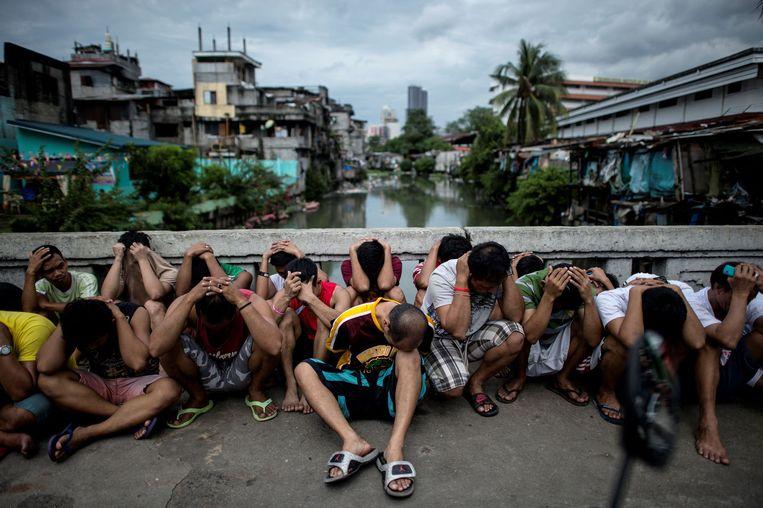 Arrestanten tijdens een anti-drugsoperatie van de Filipijnse politie bijeengedreven op een brug in Manila, 2016. Beeld AFP