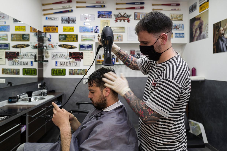 Italiaanse kappers geven bij de fiscus gemiddeld een maandinkomen op van 1091 euro. Econoom en tv-journalist Francesco Vecchi gelooft er niks van.  Beeld NurPhoto via Getty Images