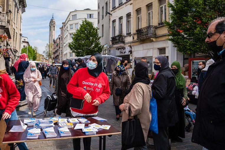'Ambassadeurs' informeren de man in de straat en trachten hen te overtuigen om zich ter plekke te laten registreren voor een vaccin.  Beeld Wouter Van Vooren