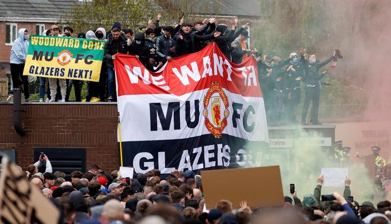 Manchester United-supporters ergeren zich groen en geel aan de Amerikanen. 'Glazers out' staat onderaan het spandoek. Beeld REUTERS