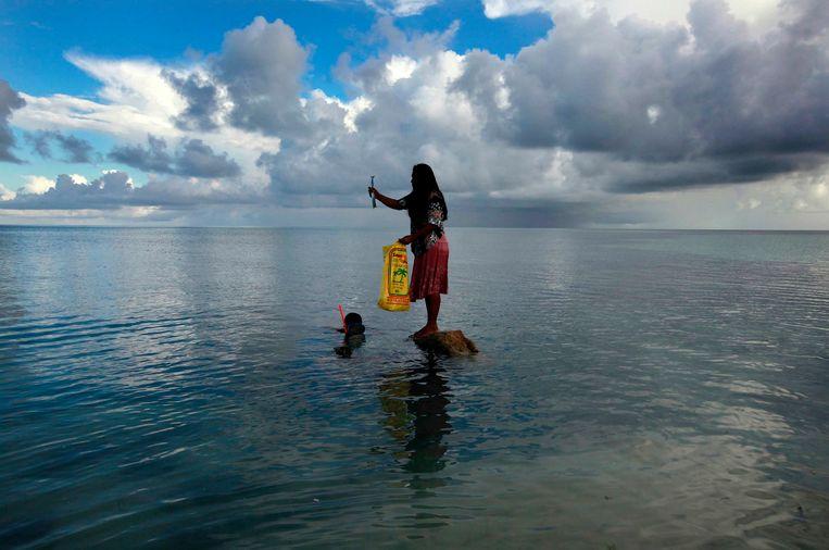 Een vrouw staat op een rots terwijl haar man vist op Bikeman, één van de Kiribati-eilanden in de Stille Oceaan die slechts enkele meter boven het zeeniveau uitkomen.