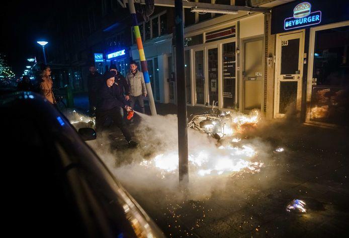 Een man probeert een brand te blussen nadat een grote groep jongeren de confrontatie heeft gezocht met de politie op de Beijerlandselaan in Rotterdam.
