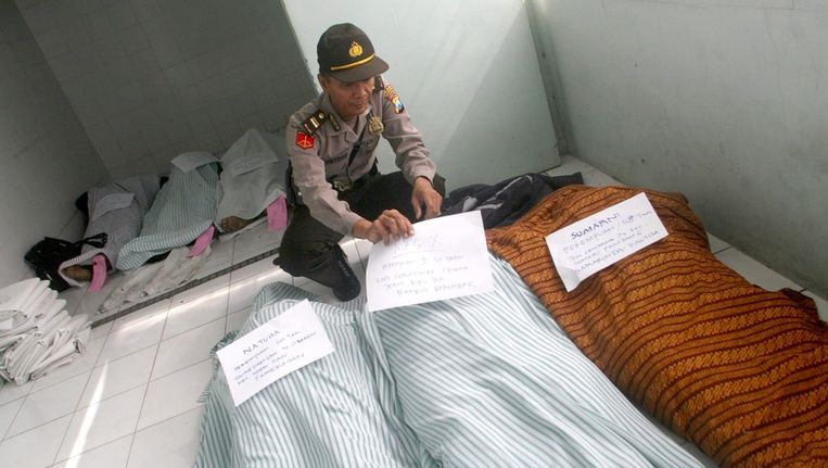 Een agent plaatst briefjes met de gegevens van de slachtoffers van de brand op de lichamen. Beeld epa