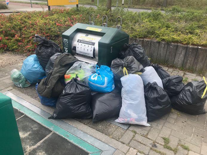 Overvolle kledingcontainers op de parkeerplaats bij de Jumbo in de Kruidenwijk in Nijverdal.