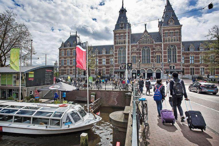 Toeristen met de zo verguisde rolkoffertjes voor het Rijksmuseum in Amsterdam, 22 april 2017. Beeld Guus Dubbelman / de Volkskrant