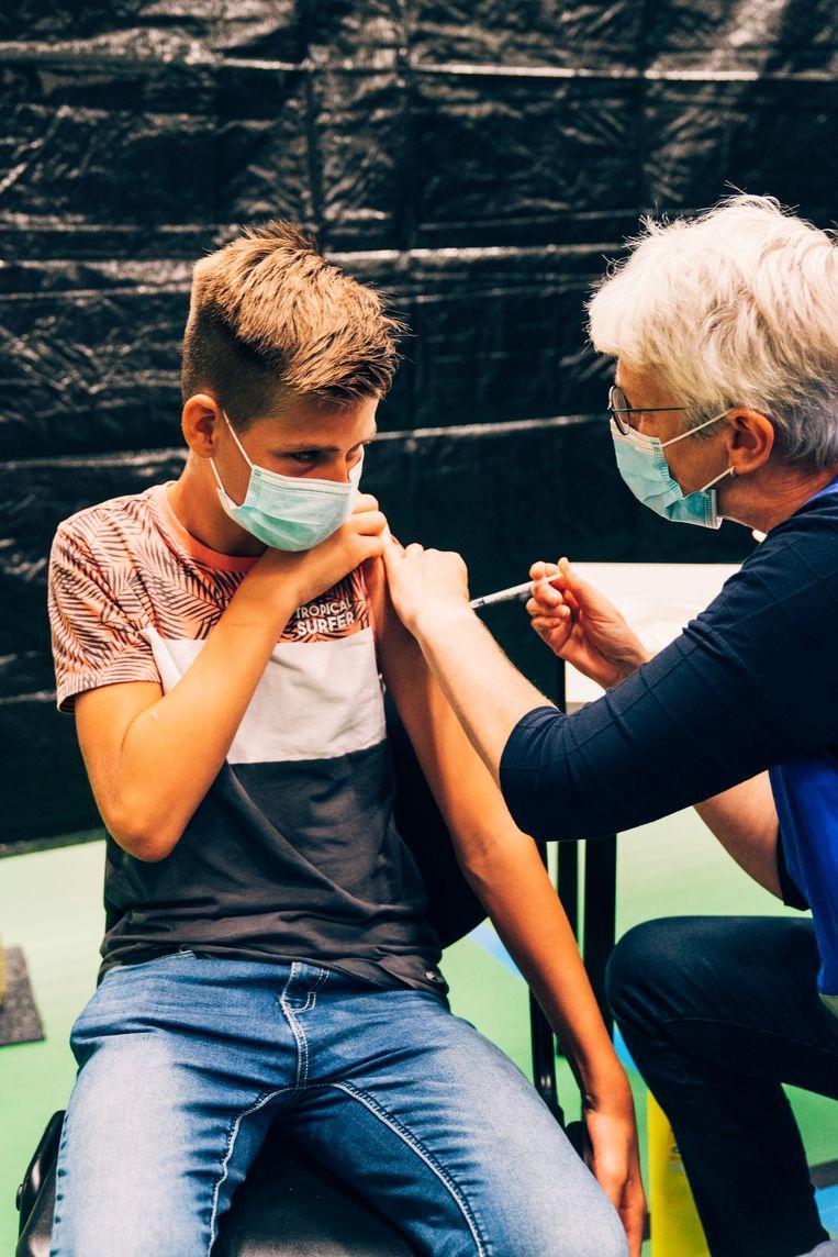 De 13-jarige Thijs krijgt een coronavaccinatie op Ameland, de eerste plek waar jongeren terecht konden om een prik te halen.  Beeld Rebecca Fertinel