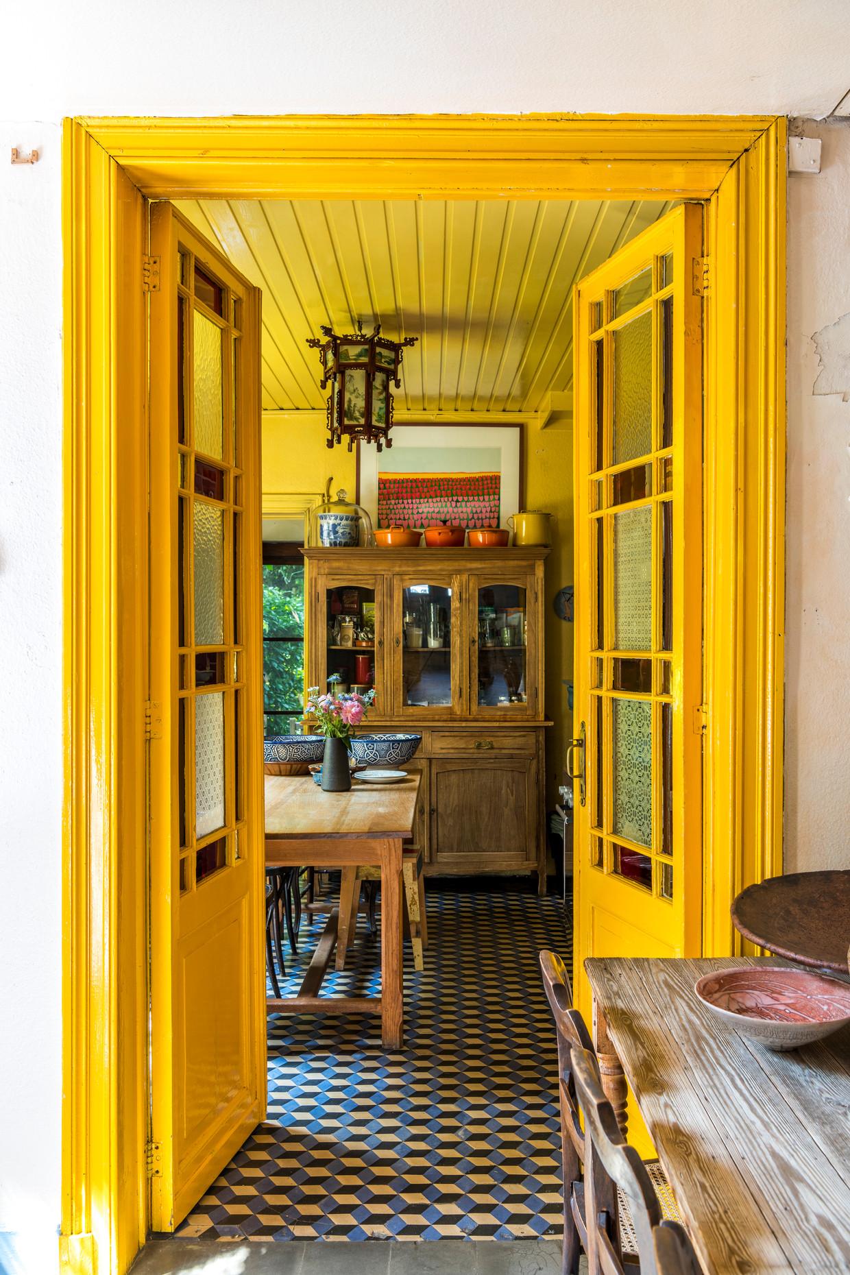 De kleurrijke keuken met uitzicht op de tuin is Jokes favoriete plek in huis. 'Het is er klein, maar gezellig. Het interieur is een bont allegaartje van antieke meubelstukken en een verzameling oude potten en pannen.'  Beeld Luc Roymans