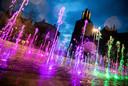 De fontein op de Markt in Arnhem wordt aangelicht in de kleuren van de regenboog.