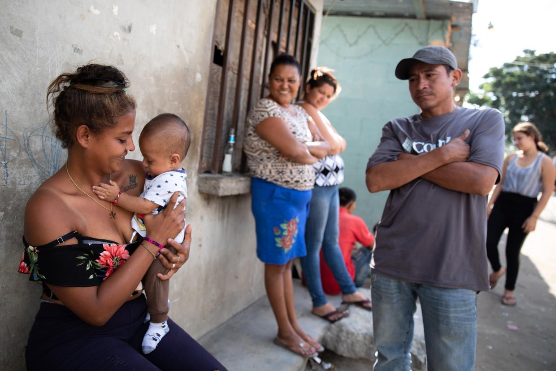 María Magdalena Diaz (links), in de hoofdstraat van Rio Blanco. Eenmaal in de VS wil ze maar één ding: 'Tien jaar hard werken en dan terugkeren.' Beeld Tomás Ayuso