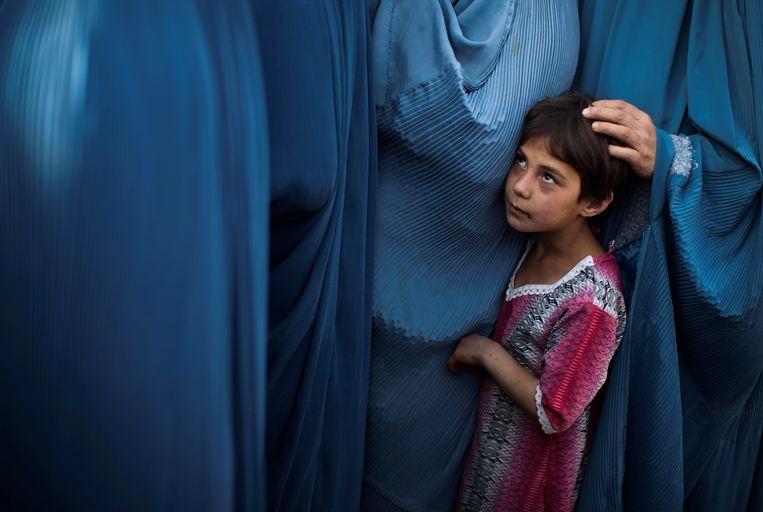 Een Afghaans meisje staat met haar moeder in de rij voor een voedselpakket in Kabul, 2010. Het Westen was van plan de positie van vrouwen te verbeteren en meisjes naar school te krijgen. In 2021 gaan er ruim 8 miljoen kinderen meer naar school dan in 2001. Beeld Reuters