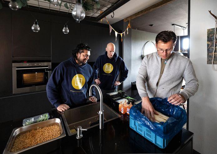 Ryan Bahadoer krijgt asperges geleverd van Don van Maaren (r), Simon de Ruiter (m) kijkt toe