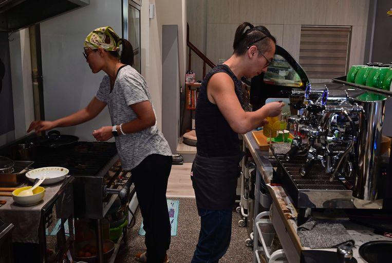 Chow Chung-ming (r) en zijn vrouw So Kit-sum bereiden eten in hun kattencafé in Taiwan.  Beeld AFP