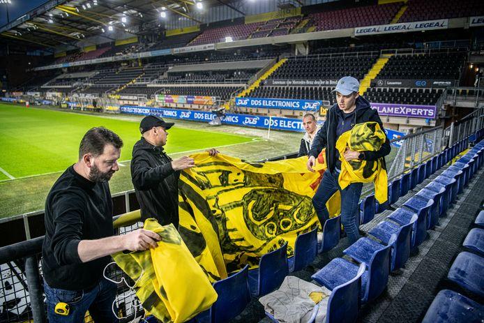 Supporters van NAC hangen spandoeken op  in een leeg stadion.