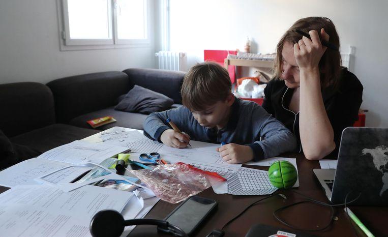 Nino Laine geeft haar zoon huiswerkbegeleiding aan de keukentafel.   Beeld Getty Images