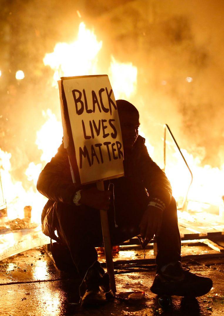 'De levens van zwarten doen er toe', staat op het bord van een demonstrant in het Amerikaanse Oakland. Beeld REUTERS