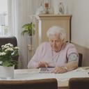 Een oudere dame beeldbelt via de iPad met haar zorgverlener: een voorbeeld van zorg op afstand.