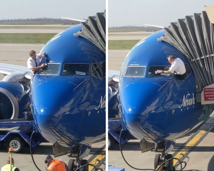 Des pilotes de ligne nettoient le pare-brise de leur avion avant de décoller.