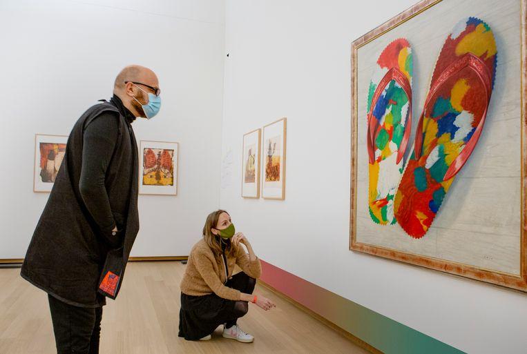 Gastcurator Bart Krieger en curator Claire van Els bekijken het schilderij Chinese slippers (1980-1983) van Jules Chin A Foeng. Beeld Pauline Marie Niks