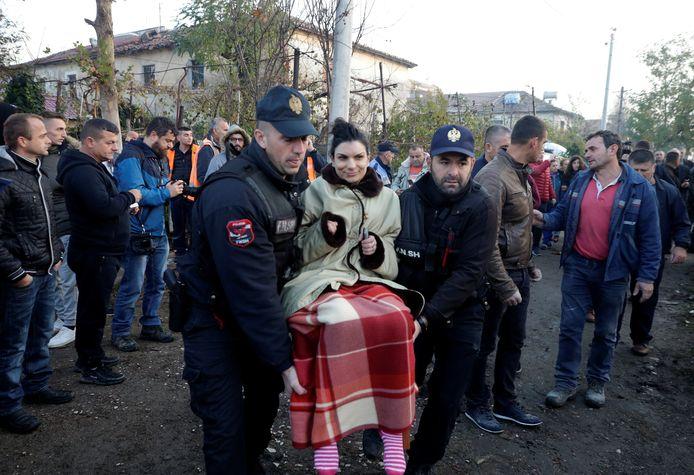 De politie brengt een geredde vrouw in veiligheid.