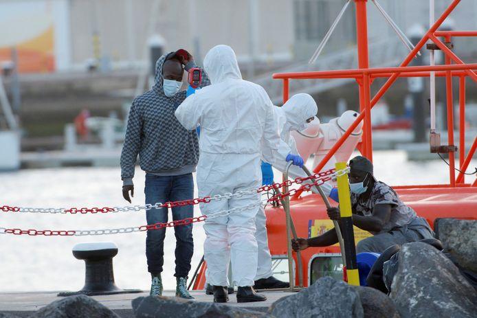 Een reddingswerker meet de temperatuur van de gearriveerde migranten.