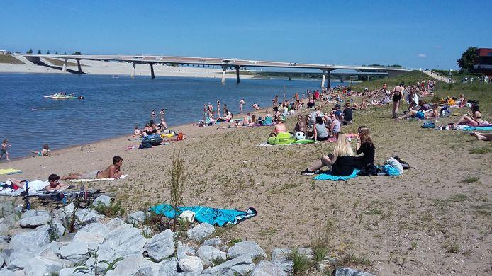 Tientallen genieten van de zon op één van de Waalstrandjes in Nijmegen.