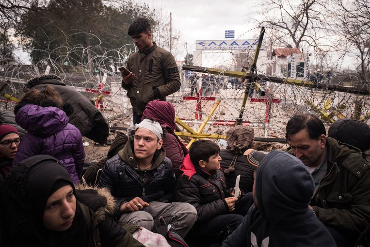 Honderden vluchtelingen proberen de Griekse grens over te steken, maar de toegang is afgeschermd met rollen prikkeldraad.  Beeld Zolin Nicola