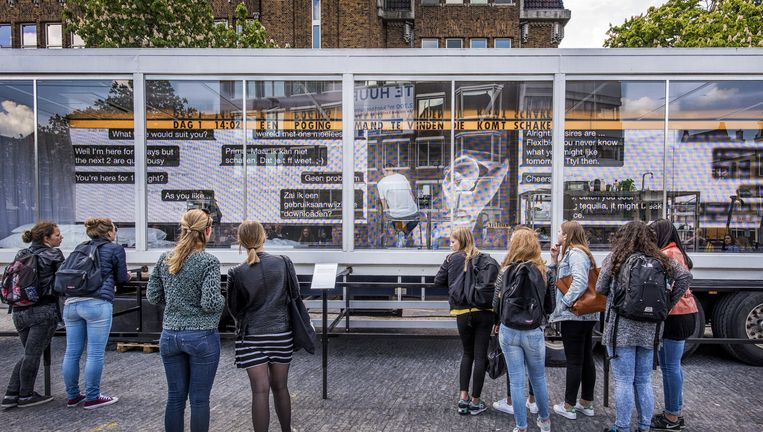 Dries Verhoeven in zijn transparante container op de Neude in Utrecht. De chatsessies zijn van buitenaf zichtbaar. Beeld Raymond Rutting
