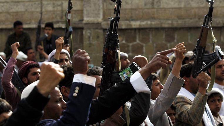 Gewapende Houthi-aanhangers scanderen anti-Saoedische leuzen tijdens een protestmars in Jemen. Beeld EPA