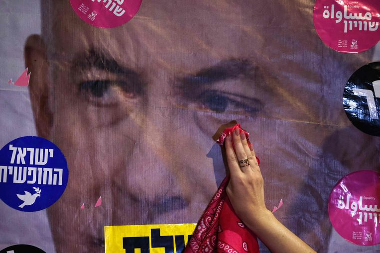 Een Israëlische demonstrant veegt een traan af van een poster waarop premier Benjamin Netanyahu is afgebeeld.  Beeld AFP