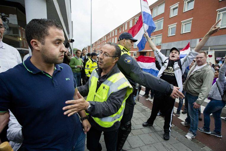 Demonstranten worden geblokkeerd door de politie tijdens de 'Mars van de vrijheid' in de Haagse wijken Schilderswijk en Transvaal op 10 augustus. Beeld anp