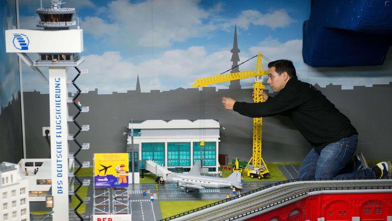 Een medewerker van het Lego Discovery Center in Berlijn werkt aan een miniatuurversie van de plaatselijke luchthaven. Binnenkort ook een mini-Schiphol in Scheveningen? Beeld AFP
