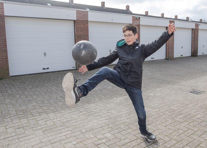 Kevin Davila voetbalt veel met zijn vrienden op een pleintje bij garages.