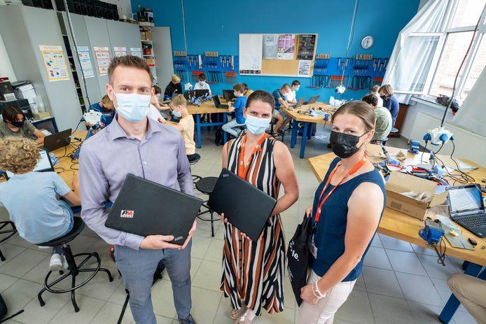 Else Boriau en Katrien Raats van PM Group overhandigen laptops aan directeur van OLVP Tom Sas