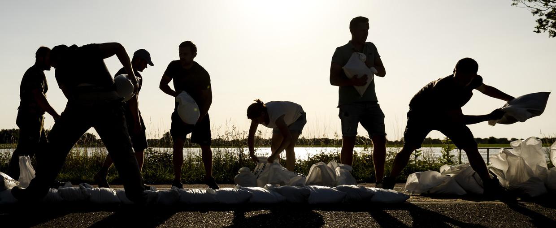 Vrijwilligers en militairen bouwen een dijk van zandzakken bij Arcen, zaterdag 17 juli.